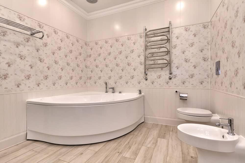 Master bathtub boasting elegant walls and a large corner tub set on the hardwood flooring.