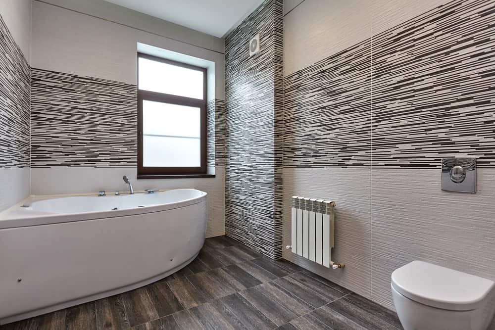 A master bathroom with stylish walls and hardwood flooring, along with a large corner tub.