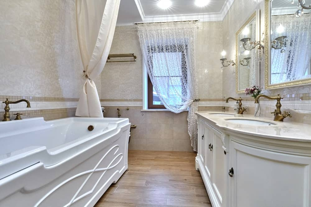 Master bathroom with luxurious walls and a double sink lighted by classy wall lights. The room offers a large freestanding tub set on the hardwood flooring.
