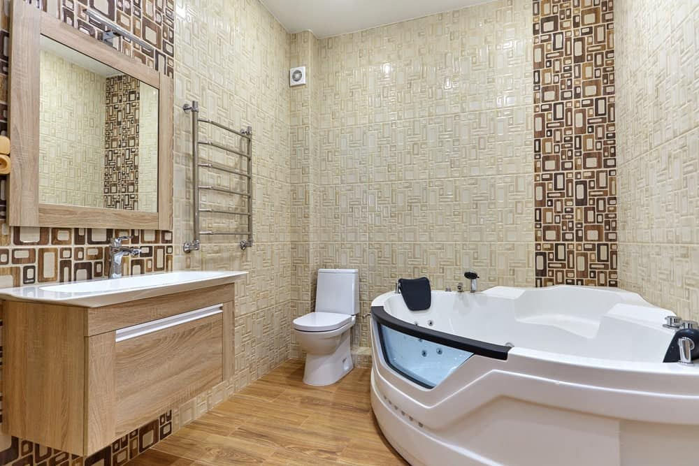 Master bathroom boasting a large freestanding tub and a floating vanity sink, along with stylish walls and hardwood flooring.