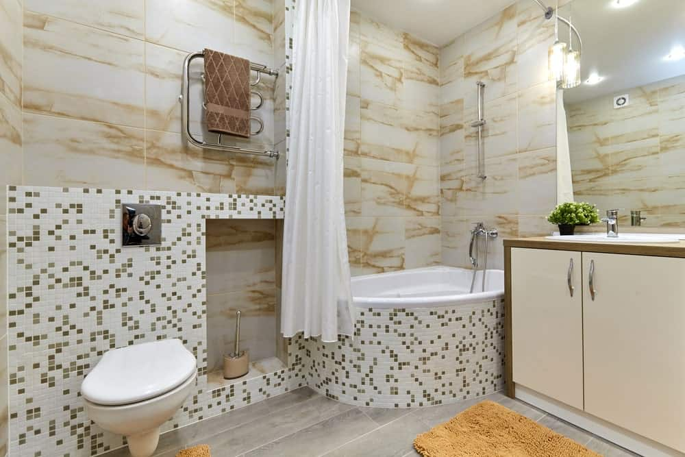 Master bathroom with a mix of mini tiles and marble tiles walls, along with hardwood flooring. The room offers a bathtub and shower combo.