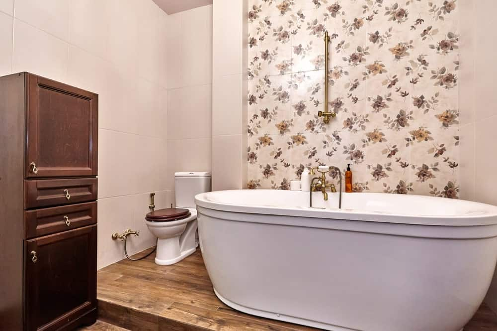 A close up look at this master bathroom's large freestanding tub set on the hardwood flooring and is next to the elegant wall.