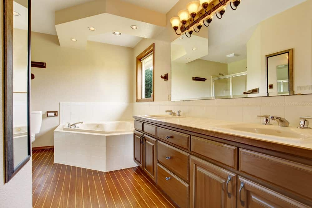 Large master bathroom with a large corner tub and a double sink, along with hardwood flooring.