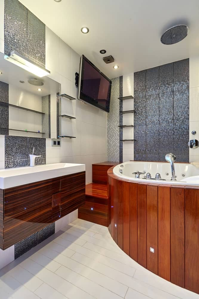 A master bathroom with stylish and rich wooden bathtub platform and stair along with the sink counter.