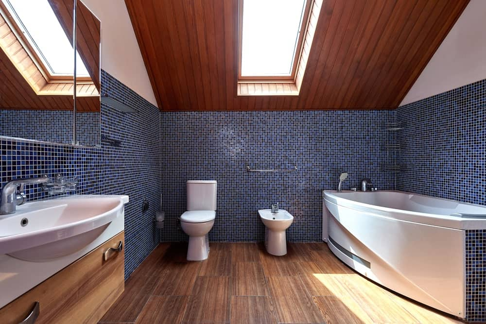 Spacious master bathroom boasting tiny black and blue tiles wall along with hardwood flooring. The room also offers a large freestanding tub.