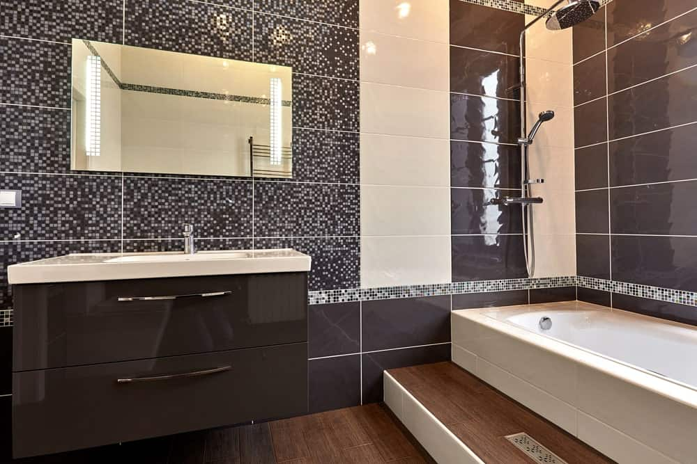 Master bathroom featuring stylish tiny tiles walls along with hardwood flooring. The bathroom also offers a shower and tub combo.