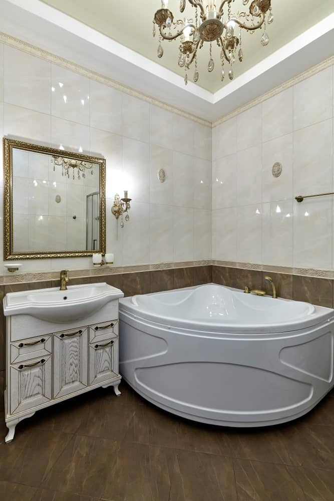 A focused shot at this master bathroom's stunning corner tub and a classy sink lighted by a glamorous chandelier.