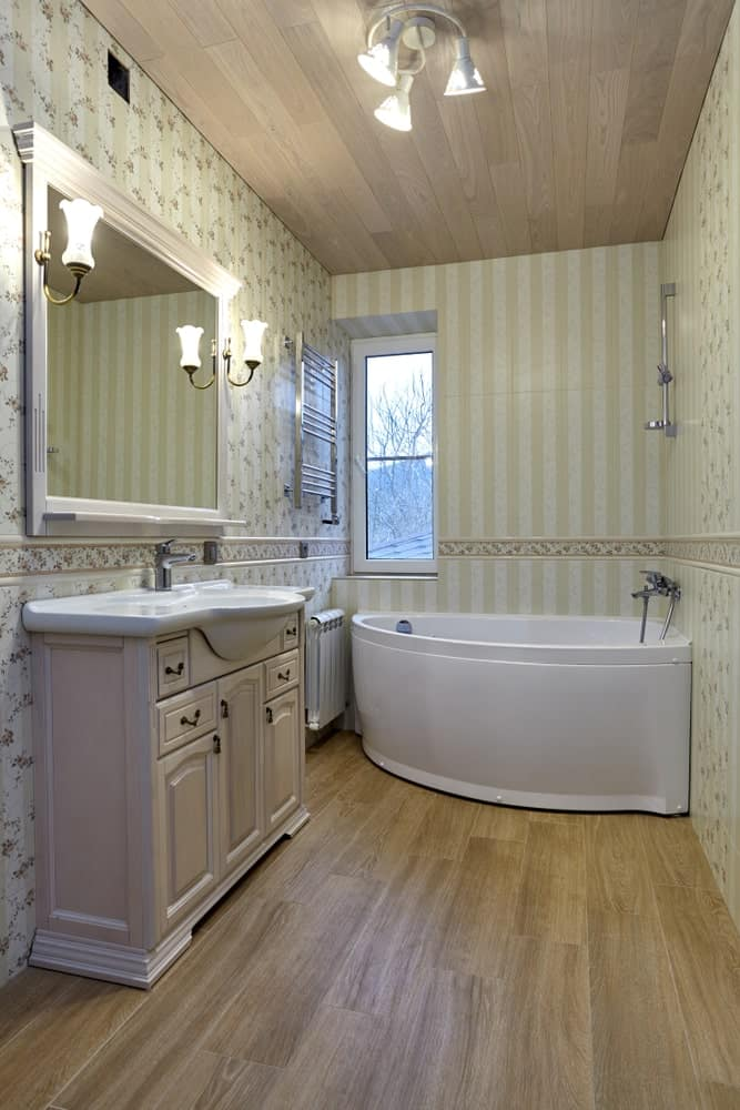 Master bathroom with classy walls and hardwood flooring, along with a large corner tub and a single sink on the side.