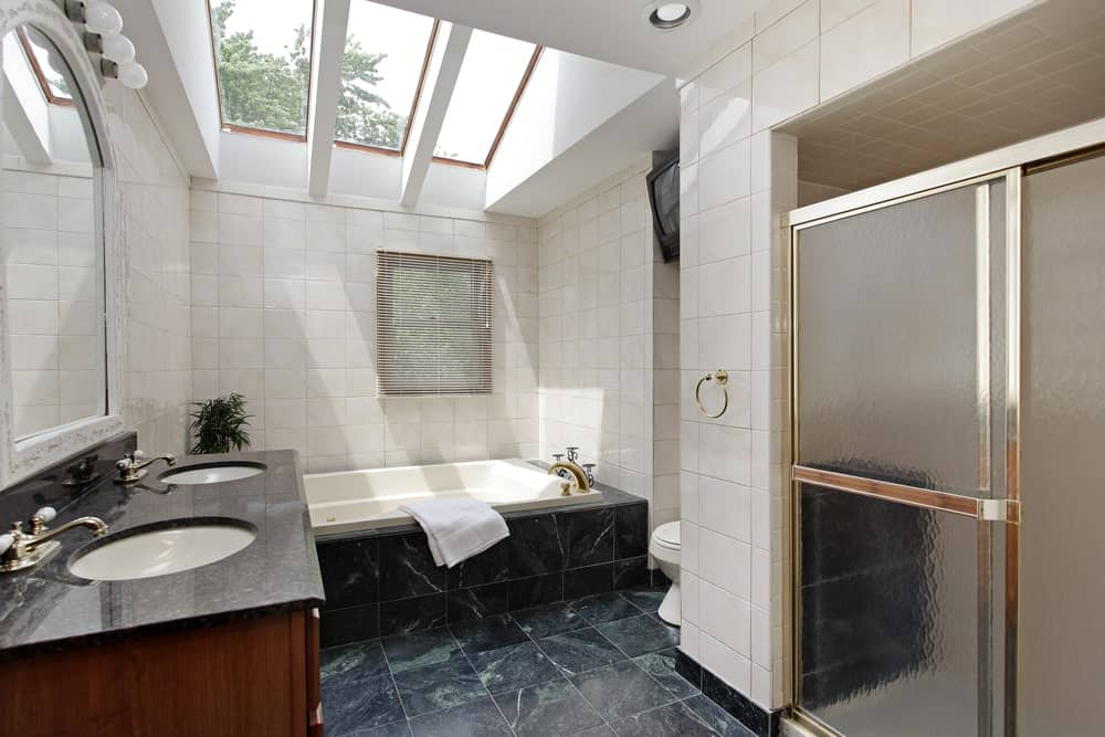 This primary bathroom boasts stylish black tiles flooring. There's a double sink, a deep soaking tub and a walk-in shower.