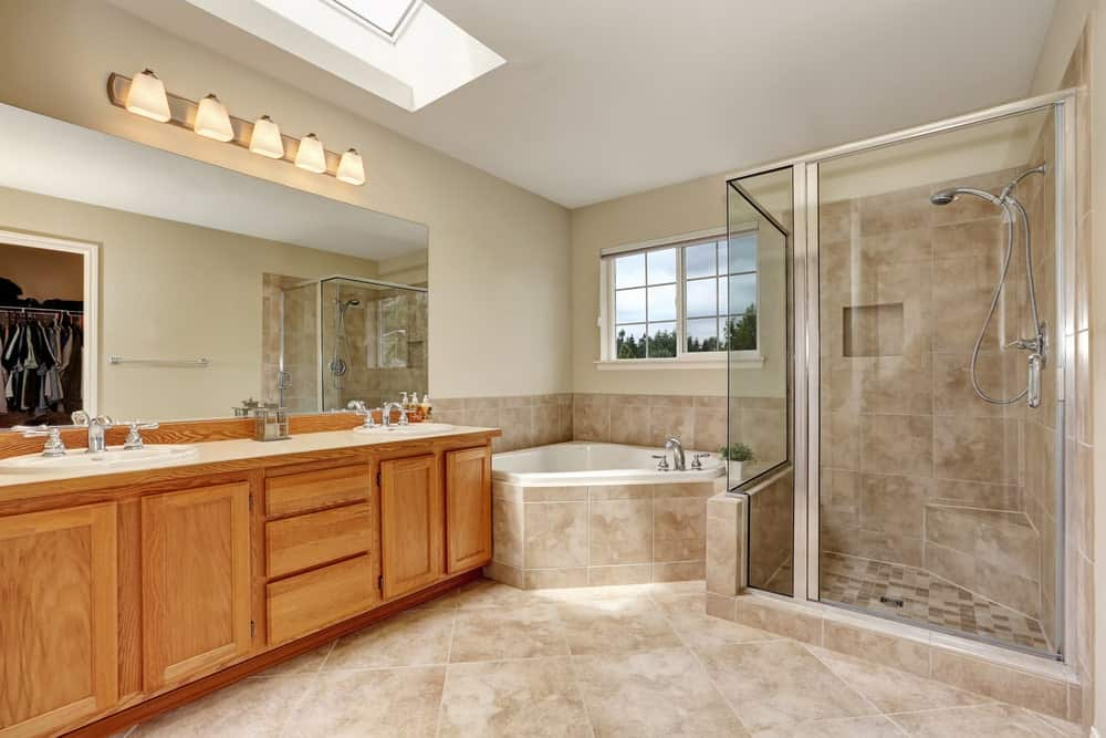 Large primary bathroom boasting a walk-in shower and a soaking tub, along with classy tiles flooring and a double sink.