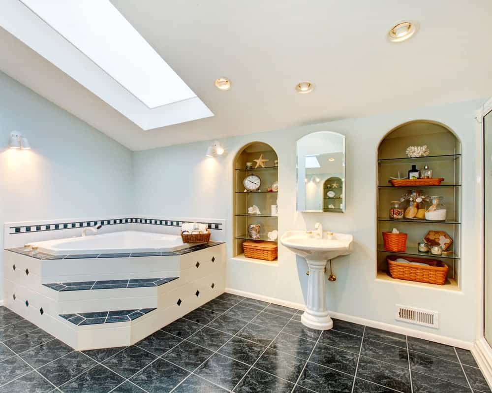 A lovely primary bathroom with stylish black tiles flooring and a stunning bathtub along with a pedestal sink in between a couple of shelves.