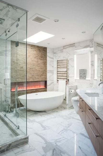 A modish primary bathroom with marble tiles floors and walls. The room also offers a freestanding tub near the large modern fireplace. There's a walk-in shower and a sink counter with marble countertop.