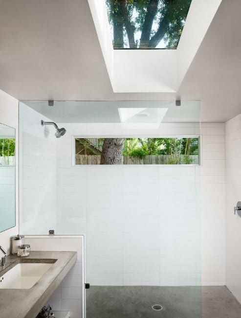 This primary bathroom offers an open shower room lighted by a skylight.