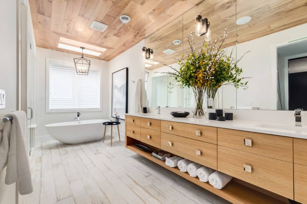 Spacious primary bathroom featuring a freestanding tub set on the hardwood flooring. The sink counter features marble countertop.