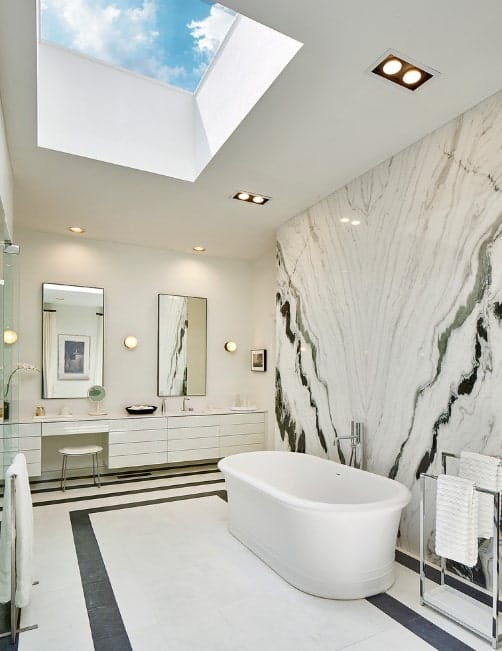 Large primary bathroom with a stunning marble wall and stylish floors, along with a freestanding tub and a walk-in shower room.