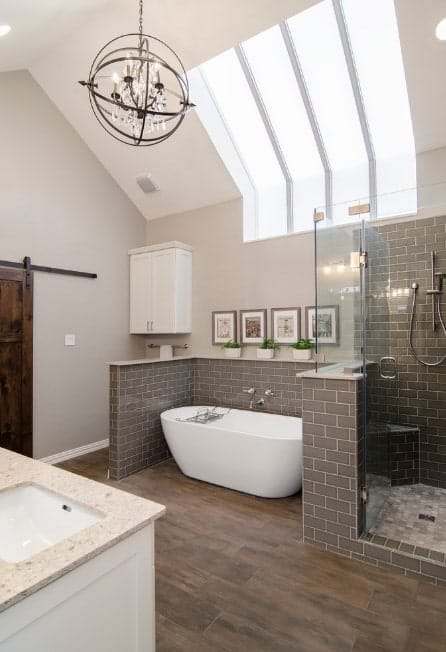 A spacious primary bathroom with a freestanding tub set on the brown hardwood flooring. There's a walk-in shower room as well.