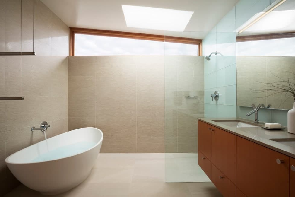 This primary bathroom offers a large freestanding tub and an open shower room along with a double sink.
