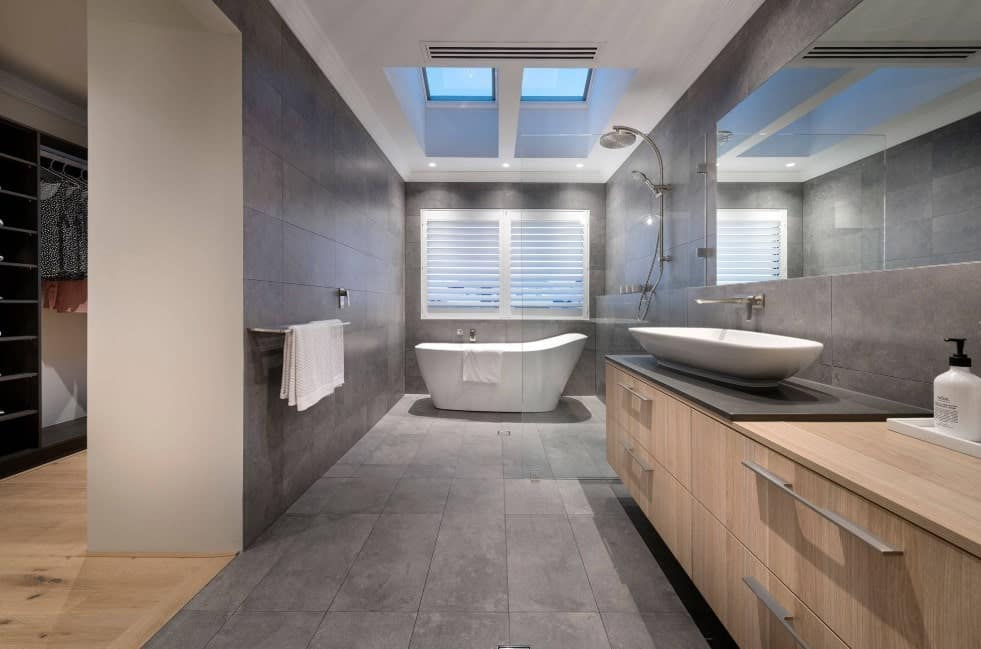 Large primary bathroom featuring a large freestanding tub and an open shower along with a vessel sink, all lighted by recessed lighting and skylights.