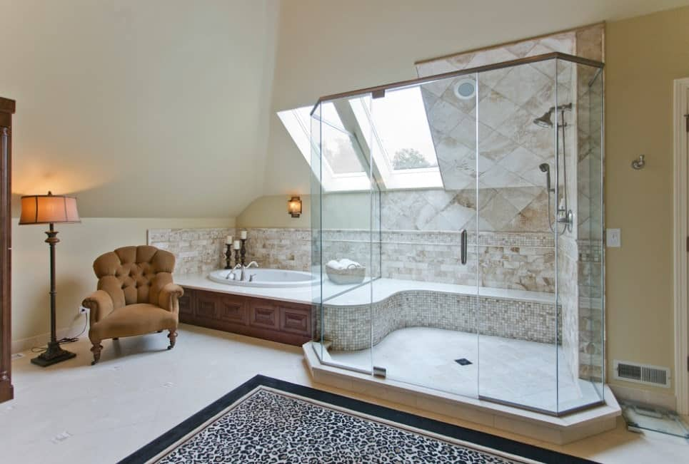 This primary bathroom offers a small bathtub and a walk-in shower. The room also offers a skylight and an elegant club chair.