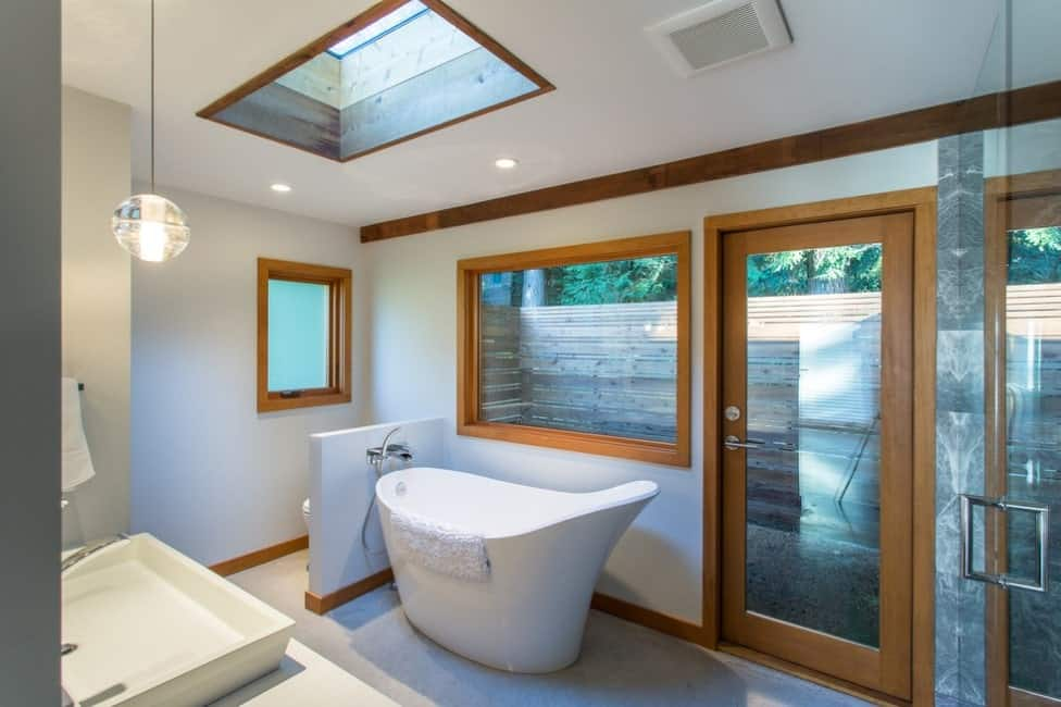 Small primary bathroom with a deep soaking tub and a vessel sink, lighted by a skylight, recessed and pendant lighting.