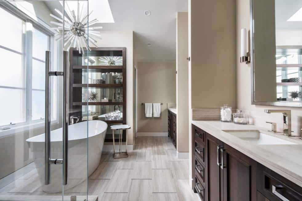 Modern primary bathroom featuring a freestanding tub set on handsome tiles flooring. The room also offers a walk-in shower.