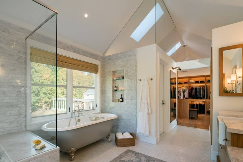 This primary bathroom offers a freestanding tub and a walk-in shower room. It also has a doorway leading straight to the home's walk-in closet.