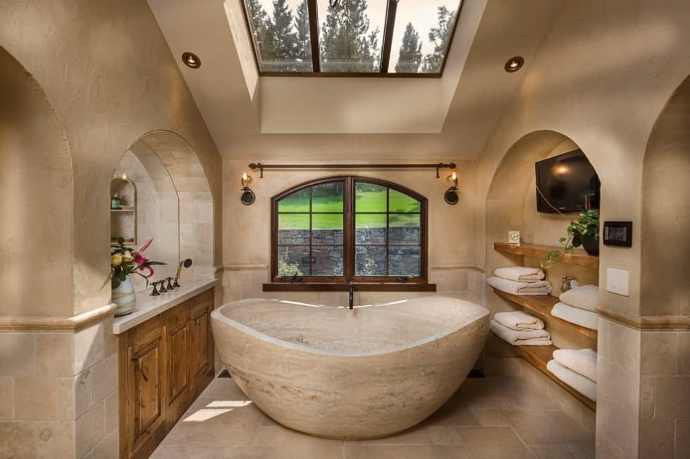 Mediterranean primary bathroom with a classy deep soaking tub under the skylight.