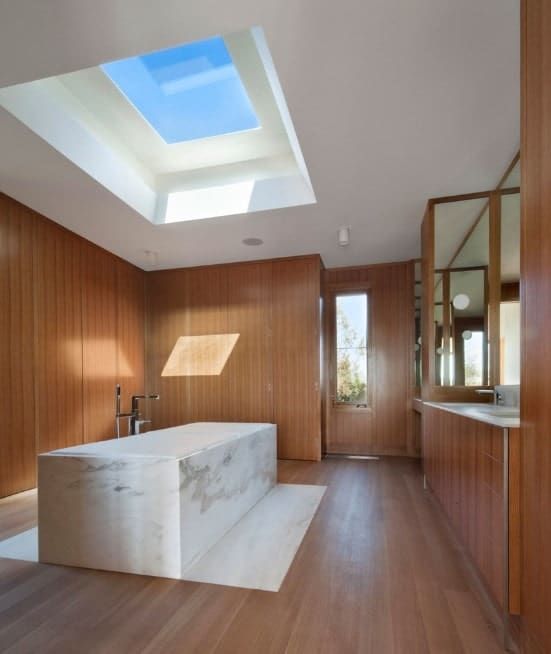 Large primary bathroom with an attractive freestanding tub under the skylight. The room also offers hardwood flooring matching the walls.