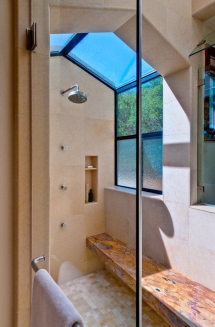 A close up look at this primary bathroom's walk-in shower featuring a skylight.