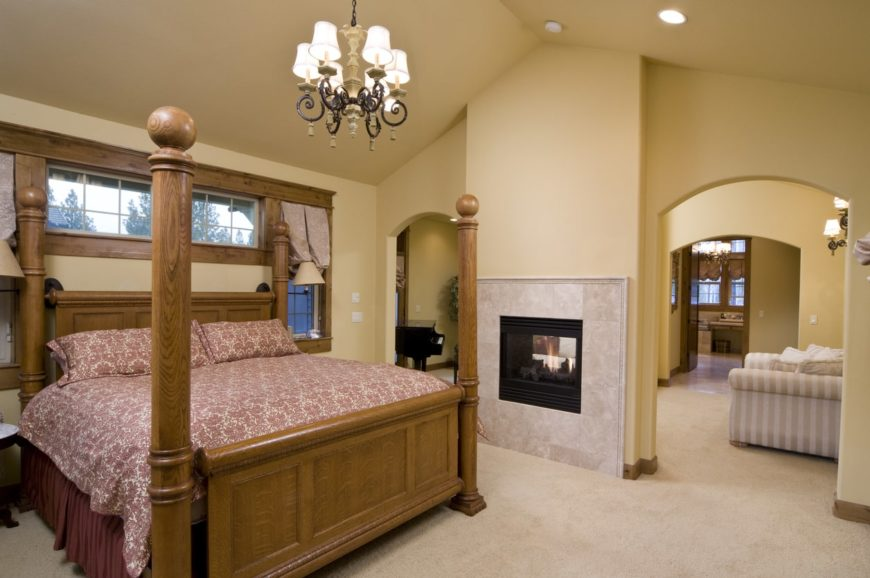 This primary bedroom boasts a large bed, a fireplace and carpet floors. The room also has its own living space with a black piano.