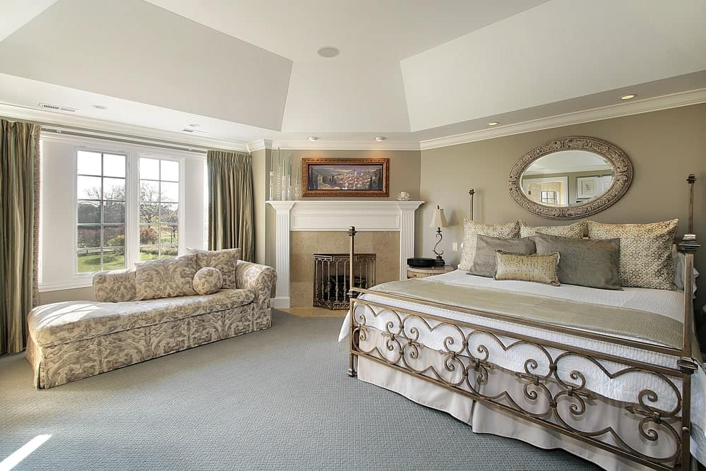 A classy master bedroom offering a large bed and a fireplace. The room features gray carpet floors and a stunning white ceiling.