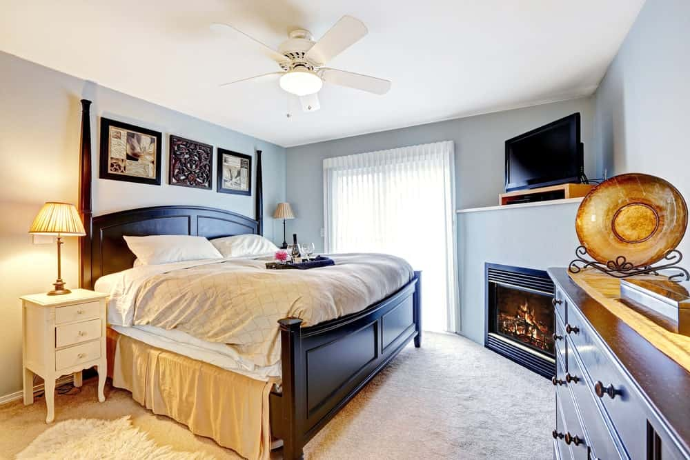 Small primary bedroom with a large bed, a fireplace, a TV on top of it and carpet floors.