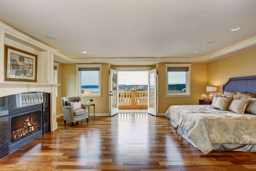 Huge primary bedroom featuring stylish hardwood floors and a fireplace, along with a large bed surrounded by beige walls. There's also a doorway leading to a private balcony.