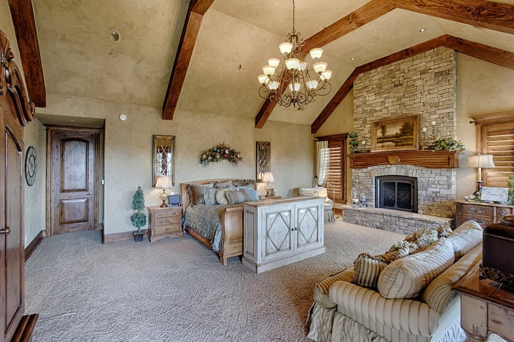 Mediterranean master bedroom with carpet floors and a glamorous chandelier, along with a classy bed and a large fireplace.