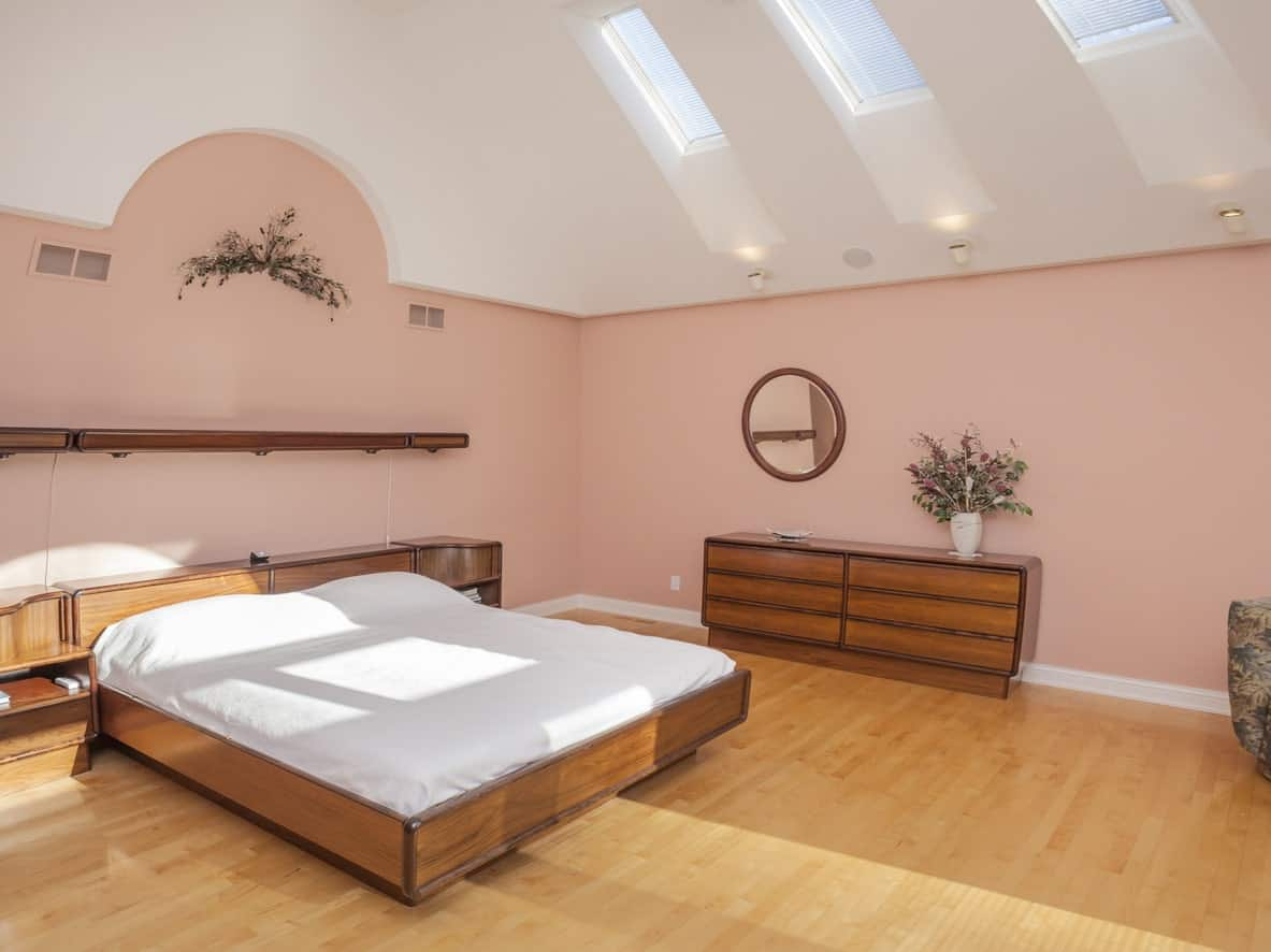 A spacious primary bedroom featuring hardwood floors and pink walls, along with a high ceiling with skylights.