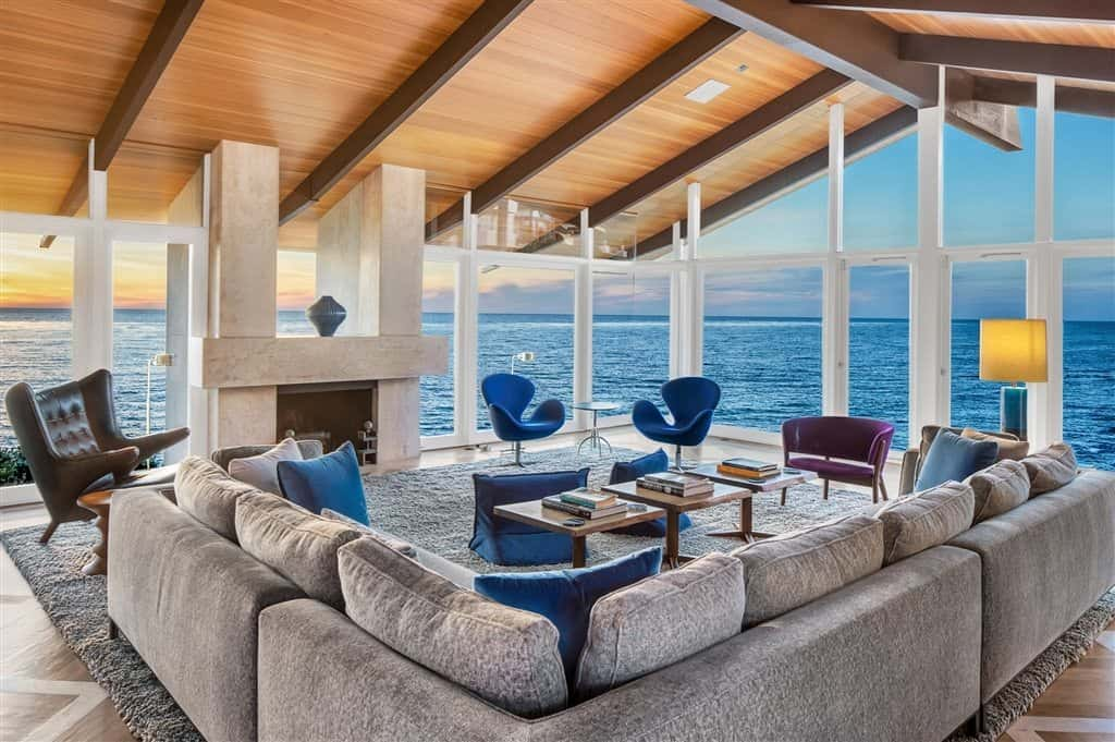 This Mid-Century Modern living room is surrounded by the brilliant scenery of the sunset and the sea featured by the glass walls. These scenery is matched by the blue velvet armchairs and the pillows of the large gray L-shaped sectional sofa.