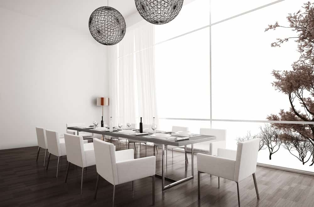 Large dining room with a long rectangular dining table set for 10 surrounded by white walls and window curtains. The brown hardwood flooring looks perfect together with the room's style.