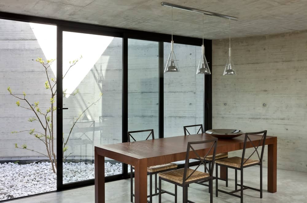 A spacious dining area with glass doors leading to the home's outdoor area. The dining table set is lighted by pendant lights.
