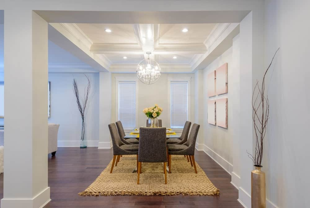 Large dining area with modern dining table set and seats on top of the classy rug covering the hardwood flooring. The area is lighted by a gorgeous chandelier set on the coffered ceiling.