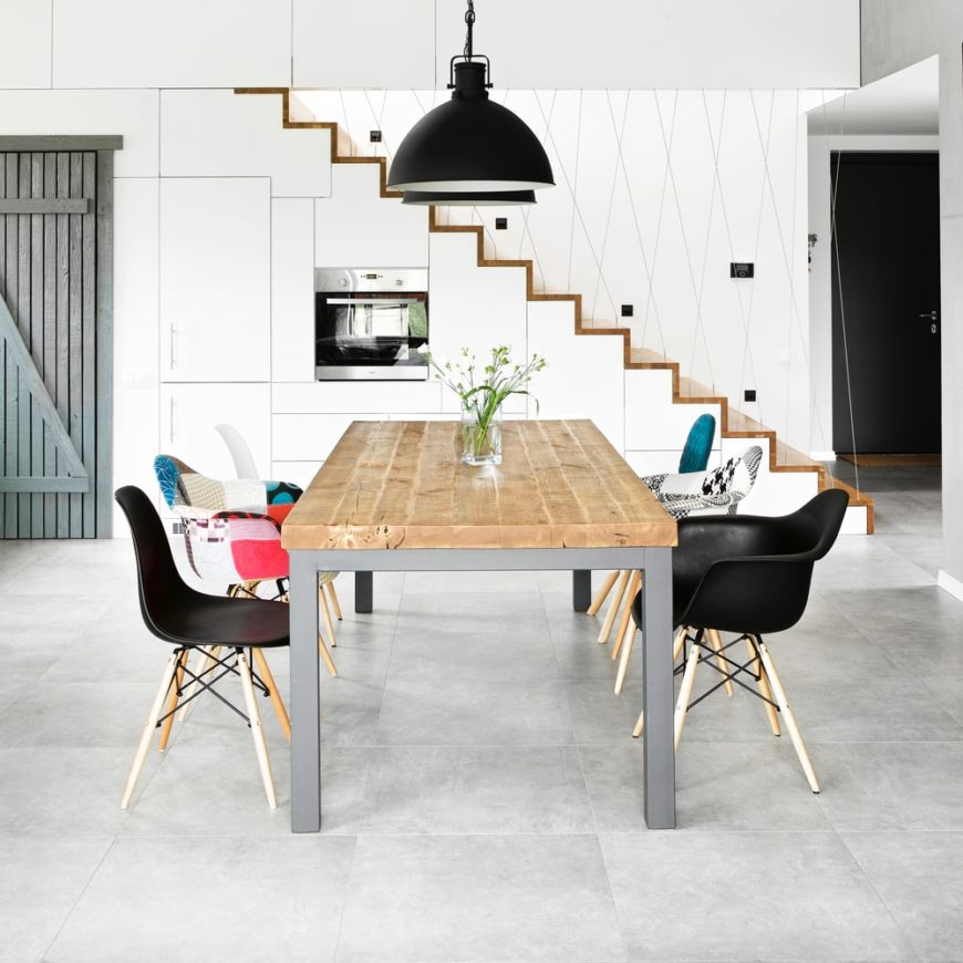 This modern dining table set is lighted by a set of handsome black pendant lights.