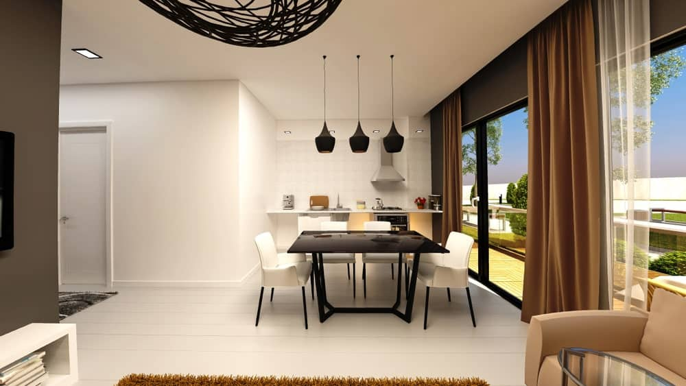 A small dine-in kitchen with a black square dining table set lighted by stylish black pendant lights.