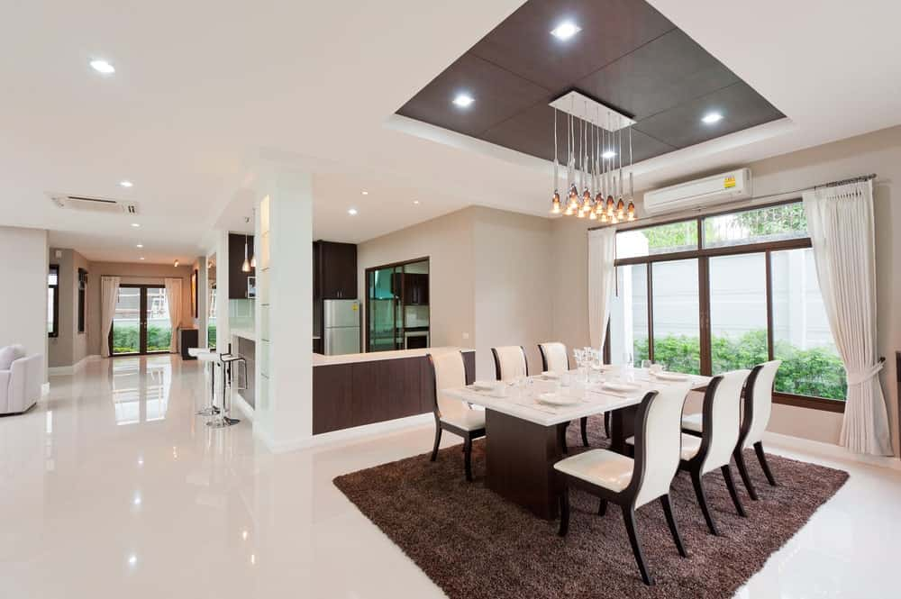 Spacious dining area with a modern dining table set lighted by classy ceiling lights hanging from the stunning tray ceiling.