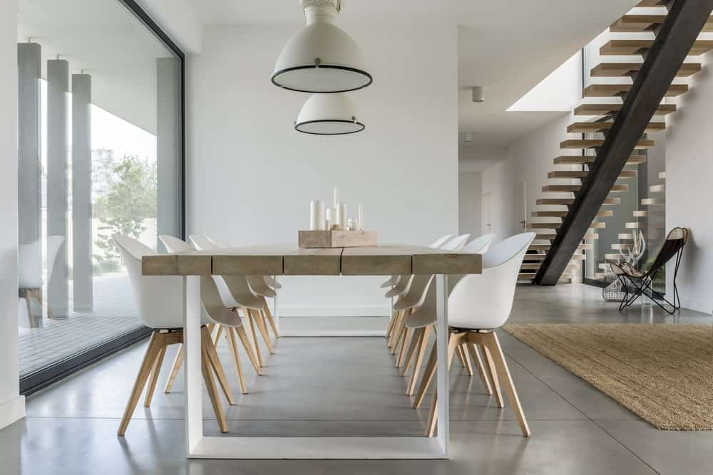 A close up look at this modish dining table set on top of the large tiles flooring lighted by a couple of pendant lights.