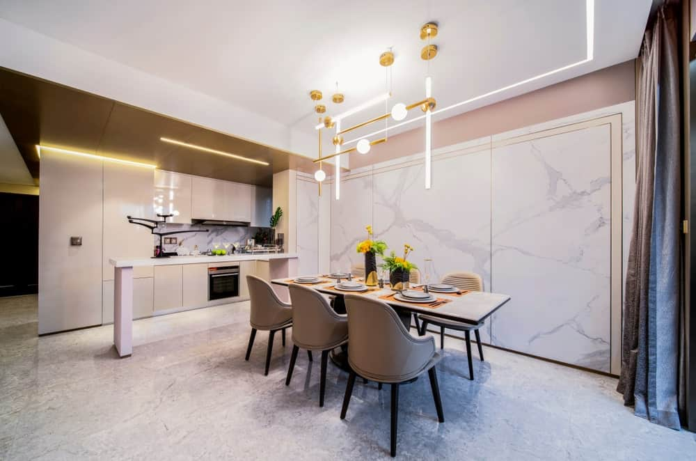 A dine-in single wall kitchen with a modish dining table set lighted by a stunning ceiling lighting.