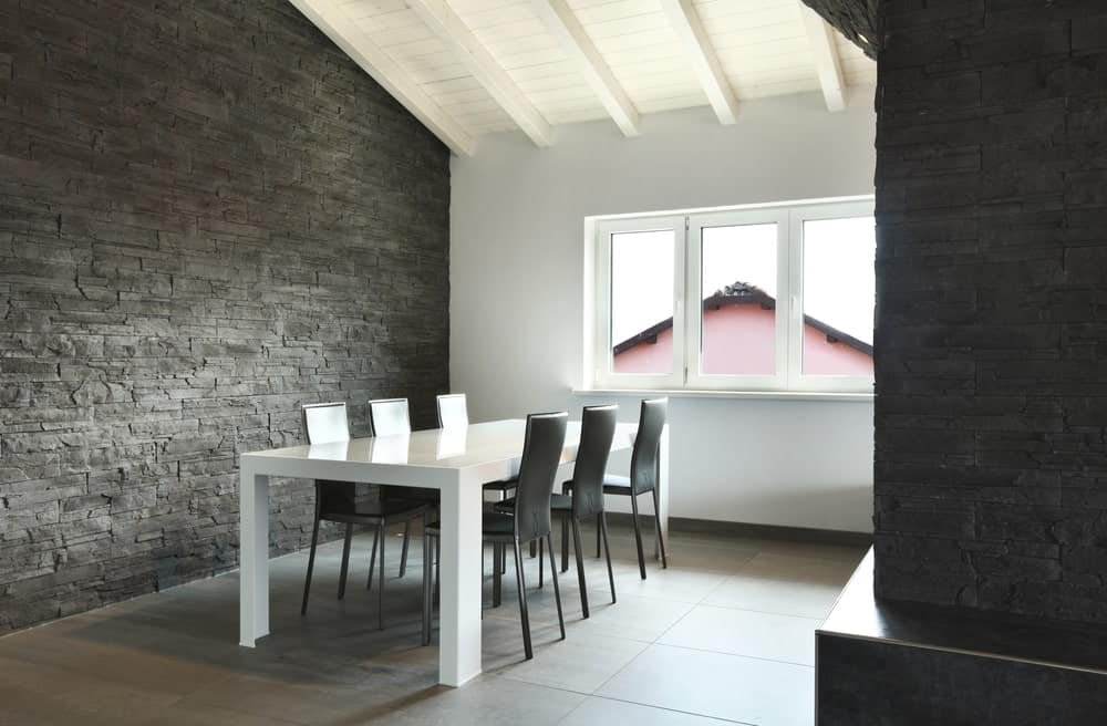 A small dining area featuring a stylish black brick wall along with tiles flooring and a white dining table.