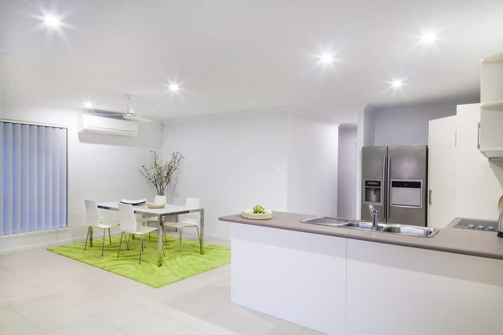 Large dine-in kitchen featuring white tiles flooring matching the white walls and white ceiling lighted by scattered recessed lights.