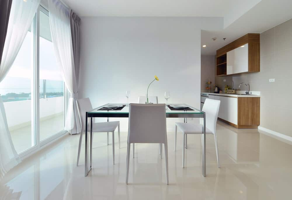 A square dining table set on top of the home's white tiles flooring. There's a doorway leading to the home's balcony.