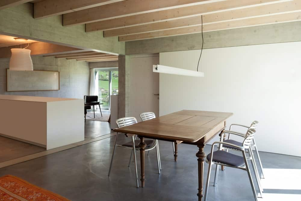 A stylish rectangle dining table set. The home features black floors and a ceiling with exposed beams.