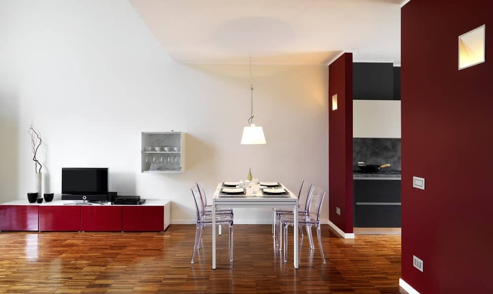 This home boasts white walls and ceiling added by red accent and brown hardwood flooring. The dining area features a glass top table and glass chairs lighted by a charming pendant lighting.