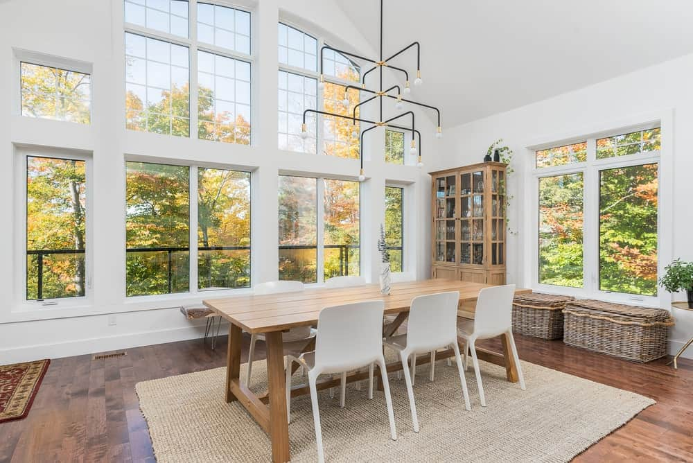 A spacious dining room with a wooden dining table matching the home's hardwood flooring topped by a rug. The room is lighted by a stunning ceiling lighting.